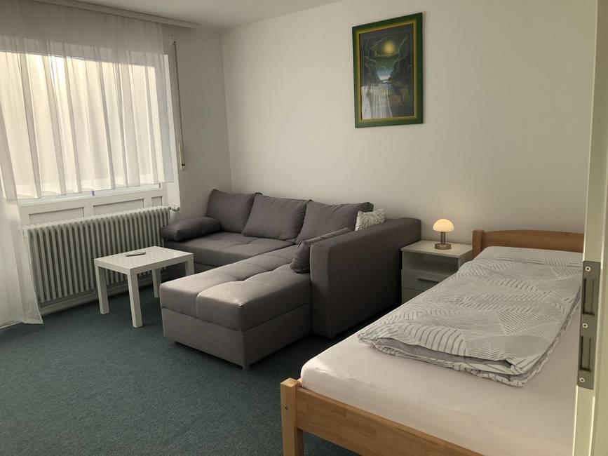 Wohnzimmer mit Bett und TV