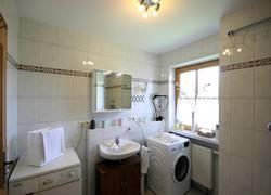 Badezimmer mit Wanne, Waschmaschine und Trockner