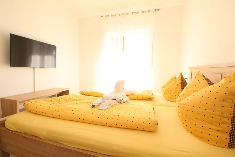 Sonniges Schlafzimmer mit Doppelbett & Smart TV
