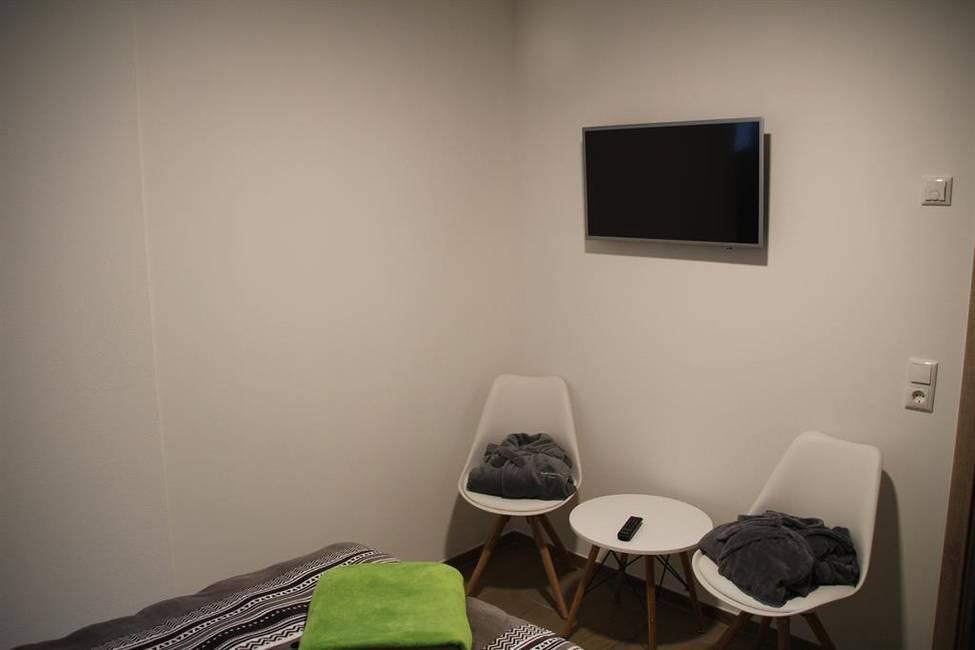Schlafzimmer mit Flat-TV u. Sitzgelegenheit