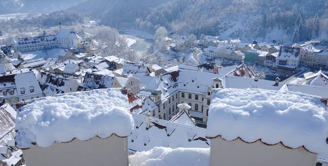 Genießen Sie in Ihrem Winterurlaub den Blick auf die verschneiten Dächer von der Füssener Altstadt.