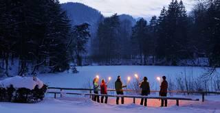 Geführte Fackelwanderung im Winter in verschneiter Füssener Landschaft